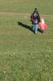 Separation. Mother and child,hand to hand, walking away. Viewed from behind in a grassland Royalty Free Stock Photo