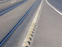 Separation barrier between tram tracks and car road Royalty Free Stock Photo