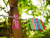 Separation of one clamp from other clamps. Close up pink clamp separation from other clamp on cloth line and blur background Royalty Free Stock Images