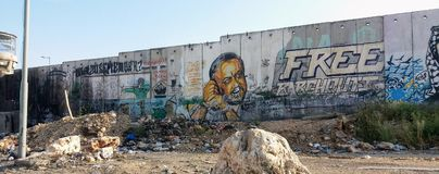 Separation wall with murals and guard house. Marwan Barghouti and fighter shooting love, painted on Palestinian-Israeli separation wall at Qalandia checkpoint royalty free stock image