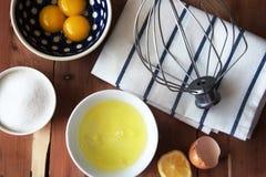 Separazione il tuorlo dell'uovo in poca ciotola ed e della preparazione per la sbattitura delle chiare dell'uovo e dei tuorli fotografia stock