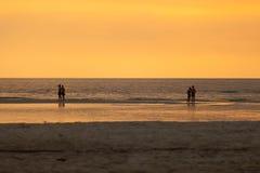 Separe a dos personas de los pares en la playa en la puesta del sol Imágenes de archivo libres de regalías