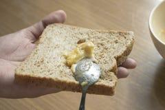 Separe la mantequilla de ajo en el pan Imagen de archivo