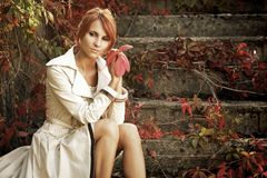 Sepia autumn. Beautiful young woman in autumn park royalty free stock photography