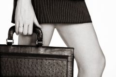 Sepia businesswoman with a case. Businesswoman in short skirt holding a case. soft sepia finish stock images