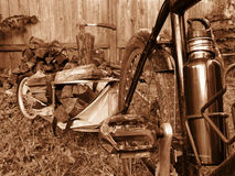 Sepia of chopping wood with hatchet and bike trailer. Sepia image of bicycle and bike trailer used to haul chopped firewood Stock Photography