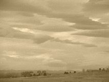 Sepia clouds over field Stock Photography