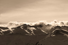 Sepia evening winter mountains and sunlight clouds Royalty Free Stock Photo