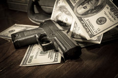 Sepia filtered of gun and dollar bills Royalty Free Stock Photo