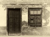 Sepia image of the facade of an old spanish house with shuttered window and old wooden door with faded plaster walls in strong s. A sepia image of the facade of royalty free stock images