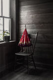 Sepia image of a red umbrella sitting on chair by the window Stock Photography