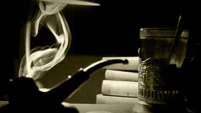 Sepia lengte van een bureau van 1930 ` s: rokende pijp, thee en een stapel boeken stock footage