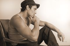 Sepia male in deep thought. Male model in deep thought he's wearing an italian fishermans cap and is seated Stock Photos