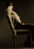 Sepia male holding chair Stock Photography