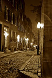 Sepia night time in boston. Sepia image of an old 19th Century cobble stone road in Boston Massachusetts, lit only by the gas lamps revealing the shuttered Royalty Free Stock Images