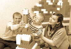 Sepia photo of happy parents building toy castle with their son Stock Photo
