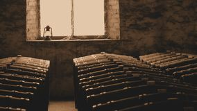 Sepia photo of historical wine barrels in window. Sepia photo of historical wine barrels in winery storage area featuring rows of oak barrels after vintage and Stock Photo
