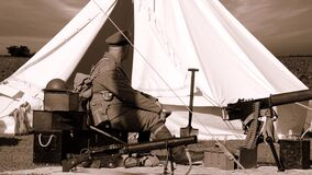 Sepia Photo of Man in Military Uniform Sitting Near Guns and White Gazebo Royalty Free Stock Photo