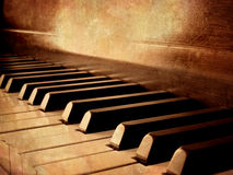Sepia Piano Keys. Closeup of black and white piano keys and wood grain with sepia tone stock image