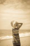 Sepia picture of a beautiful girl on vacation. Back view of female looking at open sea Stock Photography