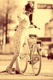 Sepia portrait of a girl with bike Stock Image