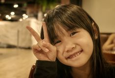 Sepia Portrait of a Little Asian Girl With Gesturing a Peace Sign royalty free stock photos