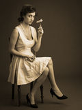 Sepia portrait of young woman sitting holding a gerber a flower. Sepia vintage  full body portrait of young woman holding a gerber a flower looking at the camera Royalty Free Stock Photos