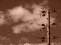 Sepia Power Lines With CLouds. Sepia toned image showing powerlines/ phone lines, on wooden pole, high in the sky , holyoke, massachusetts Stock Image