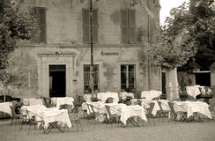 Sepia Restaurant. A quaint restaurant exterior with tables set and waiting for diners in the South of France. Sepia Toned Stock Photography