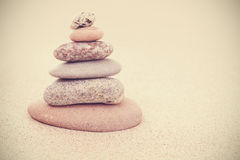 Sepia retro stylized stone pyramid on sand, harmony and balance Stock Image