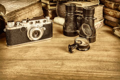 Sepia styled image of camera with compass and books Stock Photography