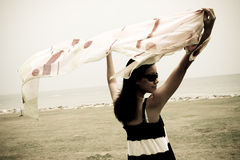 Sepia summer. A girl with a shawl standing by the windy sea Stock Images