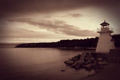 Sepia tonad fyr på kustlinjen Arkivbild