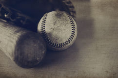 Sepia tone baseball image with vintage texture, shows bat, ball and glove. Old wooden bat showing grains laying beside vintage ball and leather mitt.  All Stock Image