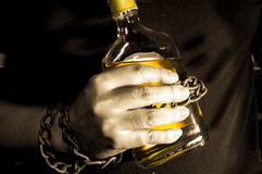 Sepia tone filtered slave to alcohol concept. Royalty Free Stock Photo