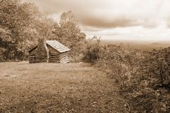Sepia Tone Image de uma cabana rústica de madeira, de um vale e de umas nuvens tormentosos imagens de stock royalty free