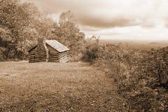 Sepia Tone Image eines Blockhauses, des Tales und der stürmischen Wolken lizenzfreie stockbilder
