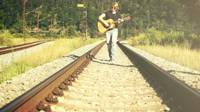 Sepia toned footage of a young man walking along the railway playing guitar stock video footage