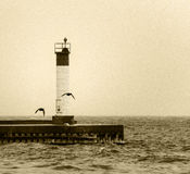 Sepia toned image of lighthouse on a pier with flying birds silh Stock Photography