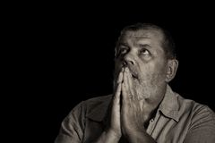 Sepia toned image of a praying senior man looking up Stock Photo