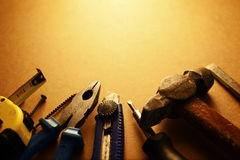 Sepia toned image of a toolkit. For home maintenance with a screwdriver, hammer, pliers, knife, tape measure and nails arranged in a semi circle with copyspace Royalty Free Stock Images