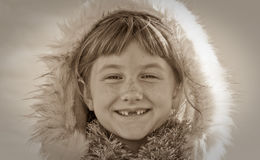 Sepia toned image of young girl haired girl wearing Eskimo styled fur trimmed hood Royalty Free Stock Images