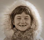 Sepia toned square format image of young girl haired girl wearing Eskimo styled fur trimmed hood Royalty Free Stock Image