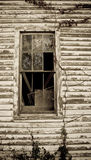 Sepia Toned Window. Sepia toned broken up window on the side of a run down old house Royalty Free Stock Photo