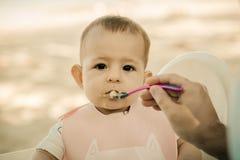 Sepia tonificado O beb? triste come o papa de aveia, sujado e o alimento no nariz O paizinho alimenta a filha pequena com uma col foto de stock
