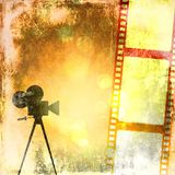 Sepia vintage background with film strip and old cinecamera. Retro style Stock Image