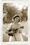 Sepia Violin Girl Antique Post. Sepia photo of teenage girl holding her violin and bow, wearing an antique party dress, outdoors. Photo is composited with an old stock photo