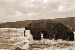 Sepia virgin rocks with storm waves Royalty Free Stock Photo