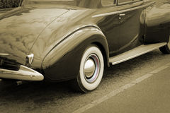 Sepia white wall tyre. Photo of a vintage car showing detail to white wall tyre and chrome wheel hub Stock Photos