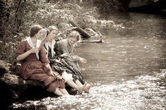 Sepia women by river creek in civil war reenactmen Stock Images